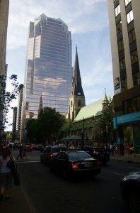 A church in downtown Montréal where you can see its steeple reflected in a nearby glass skyscraper